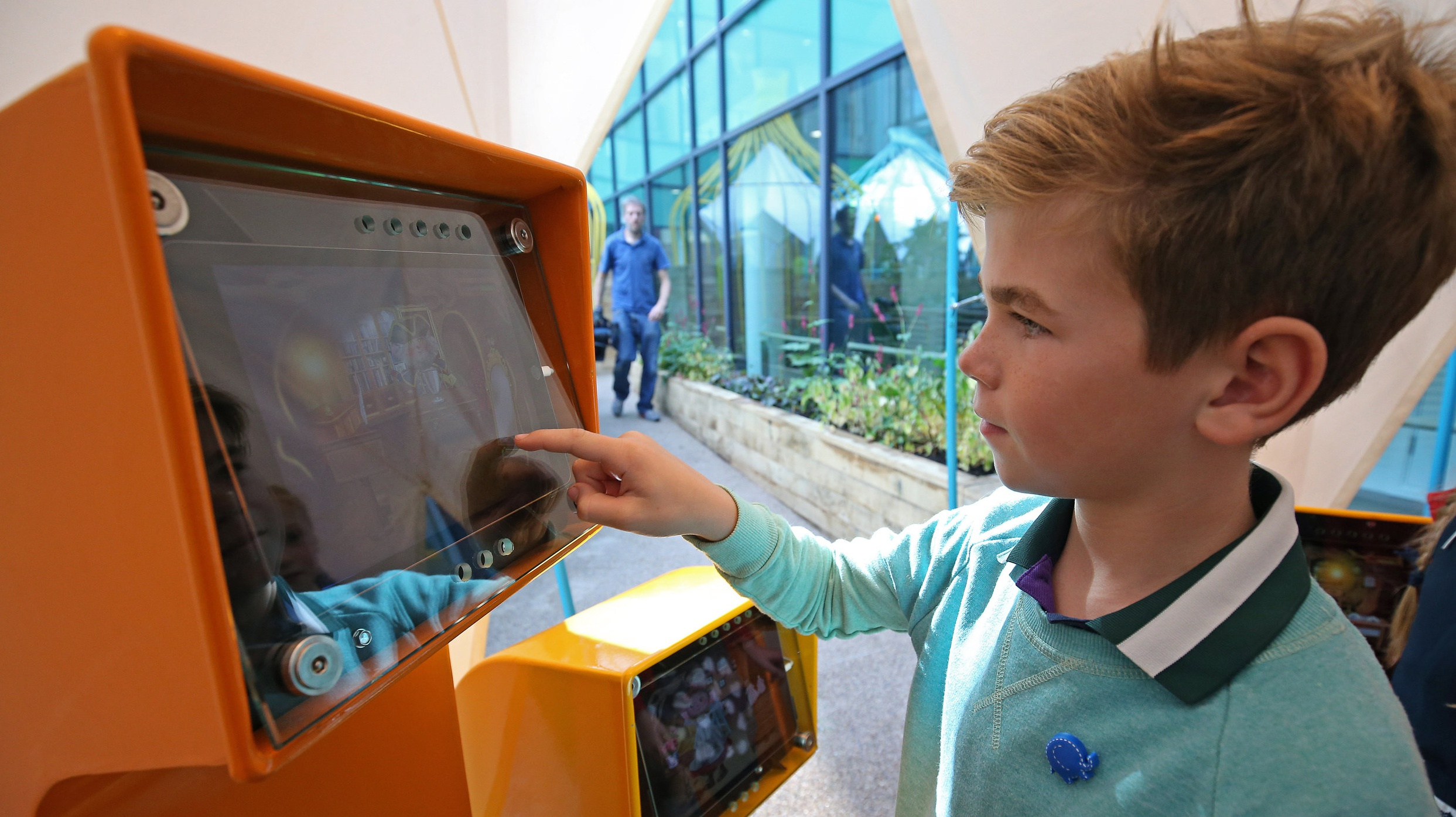 Boy playing on touch screen in garden