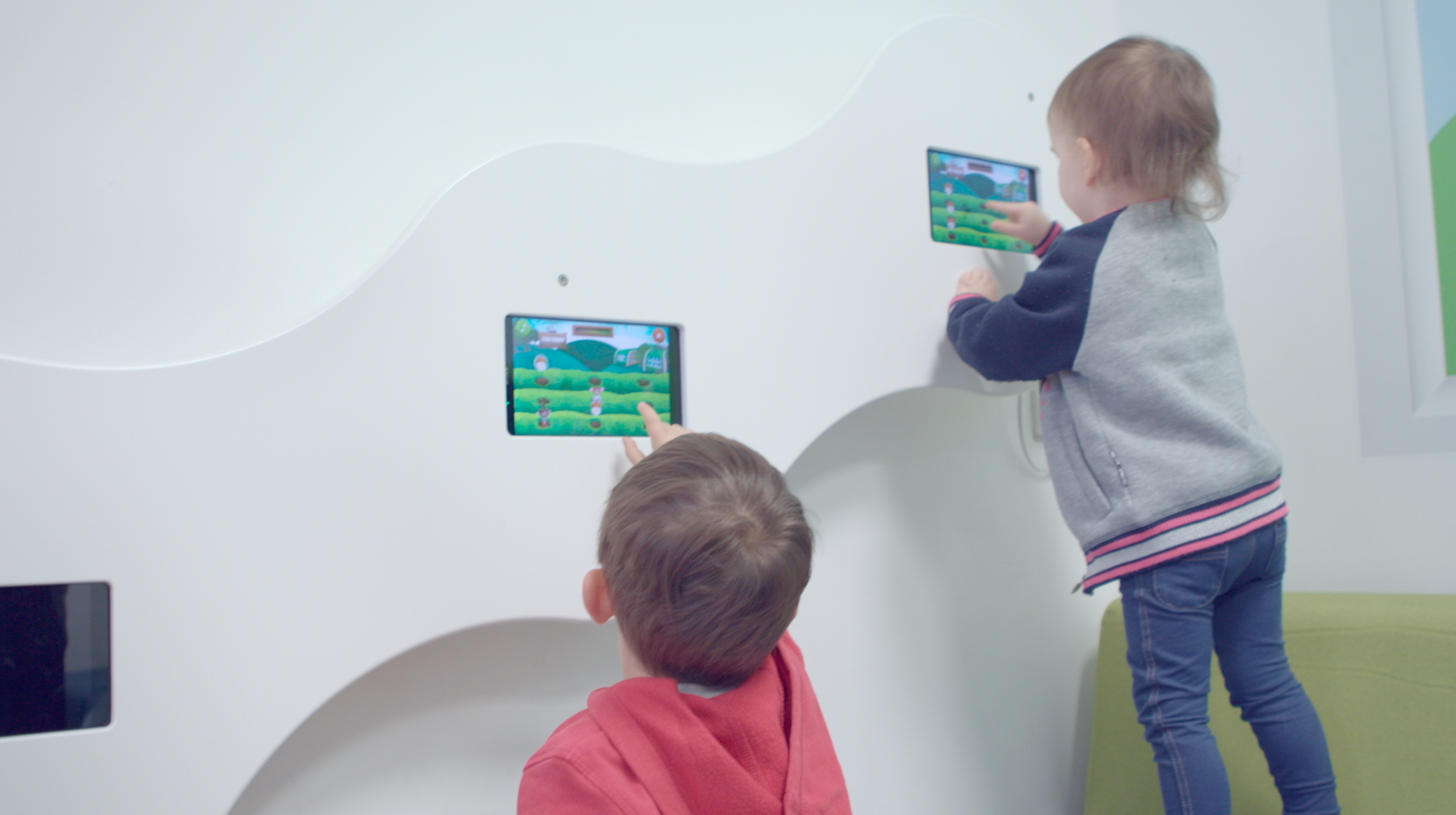 Two children playing on small touch screens