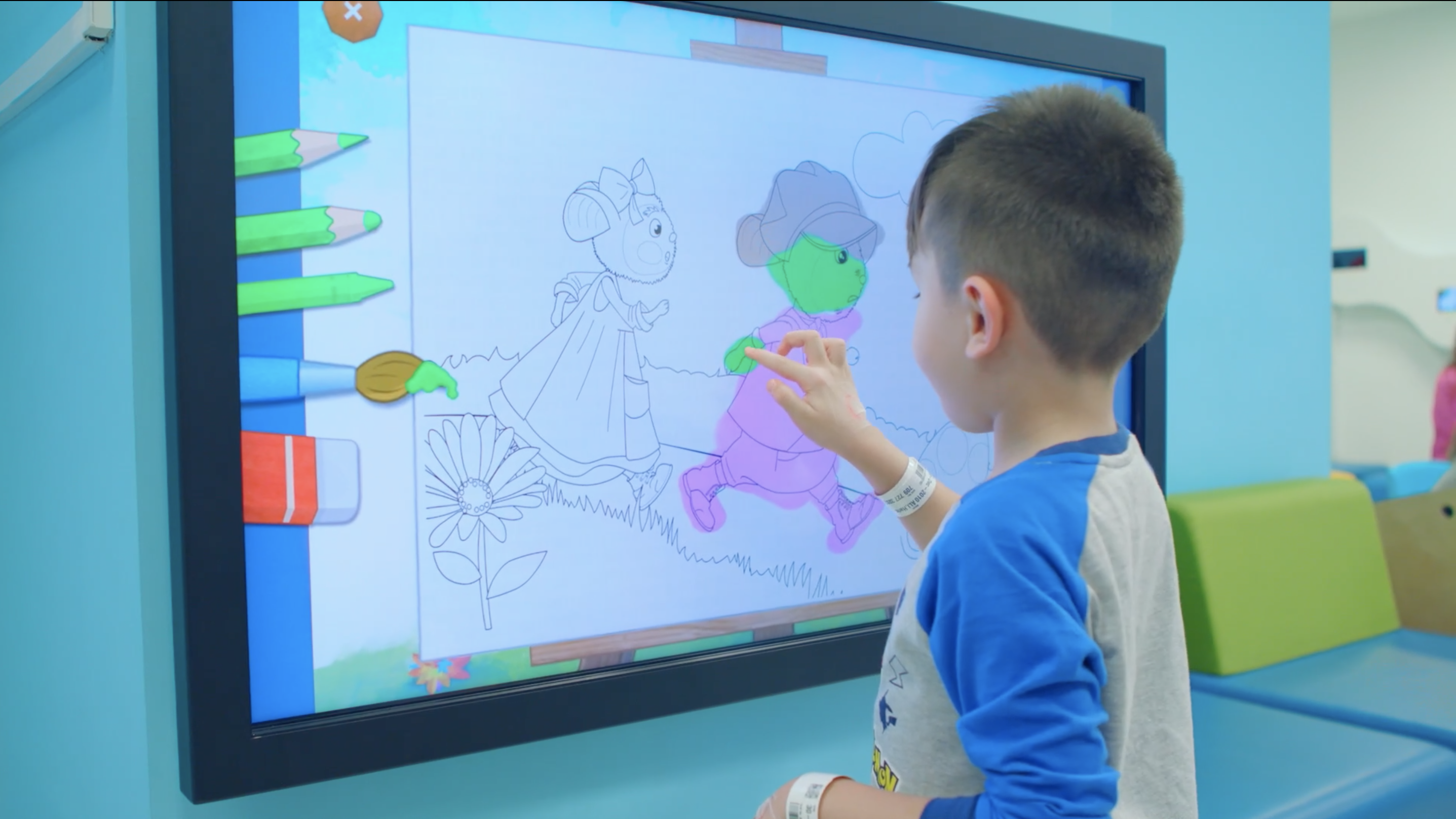 Little boy colouring on large interactive touch screen